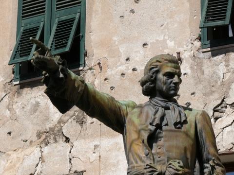 Estátua de Pascal Paoli em frente a construção com marcas de tiros