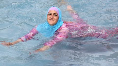 epa03366113 A young Turkish woman cools off while wearing a burkini at an open-air bath in Berlin, Germany, 20 August 2012.  EPA/STEPHANIE PILICK (MaxPPP TagID: epaphotos543477.jpg) [Photo via MaxPPP]